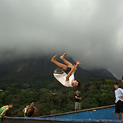 Members of  Voltz Parkour practice on the beachfront wall at Sao Conrado beach, Rio de Janeiro,  Brazil. 10th July 2010. Photo Tim Clayton..The beaches of Rio de Janeiro, provide the ultimate playground for locals and tourists alike. Beach activity is in abundance as beach volley ball, football and a hybrid of the two, foot volley, are played day and night along the length and breadth of Rio's beaches. .Volleyball nets and football posts stretch along the cities coastline and are a hive of activity particularly at it's most famous beaches Copacabana and Ipanema. .The warm waters of the Atlantic Ocean provide the ideal conditions for a variety of water sports. Walkways along the edge of the beaches along with exercise stations and cycleways encourage sporting activity, even an outdoor gym is available at the Parque Do Arpoador overlooking the ocean. .On Sunday's the main roads along the beaches of Copacabana, Leblon and Ipanema are closed to traffic bringing out thousands of people of all ages to walk, run, jog, ride, skateboard and cycle more than 10 km of beachside roadway. .This sports mad city is about to become a worldwide sporting focus as they play host to the world's biggest sporting events with Brazil hosting the next Fifa World Cup in 2014 and Rio de Janeiro hosting the Olympic Games in 2016...
