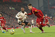 Liverpool forward Roberto Firmino (9) takes the ball past Manchester United defender Aaron Wan-Bissaka (29)  during the Premier League match between Liverpool and Manchester United at Anfield, Liverpool, England on 19 January 2020.