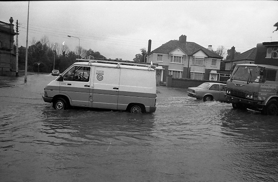 "Flooding at the Dodder..1986..26.08.1986..08.26.1986..28th August 1986..As a result of Hurricane Charly (Charlie) heavy overnight rainfall was the cause of severe flooding in the Donnybrook/Ballsbridge areas of Dublin. In a period of just 12 hours it was stated that 8 inches of rain had fallen. The Dodder,long regarded as a ""Flashy"" river, burst its banks and caused great hardship to families in the 300 or so homes which were flooded. Council workers and the Fire Brigades did their best to try and alleviate some of the problems by removing debris and pumping out some of the homes affected..Note: ""Flashy"" is a term given to a river which is prone to flooding as a result of heavy or sustained rainfall...Image of telecom workers heading out to effect repairs to systems damaged by the flood.""Keelings Fruit"" also managed to carry on with his deliveries despite the water."