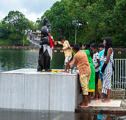 Grand Bassin, Mauritius—January 21, 2018. Family members hold a young boy steady as he stands on an altar and makes an offering to a Hindu deity.