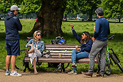 Two couples ignore the signs that say only use the benches for a short rest and also the guidance not to meet up with friends - they a presumably anticipating that such guidance is no longer relevant, given the announcement tonight - Clapham Common on the day of the Governments 'big' announcement on the possible easing of restrictions - Lambeth Council have already changed notices so that people can sit on benches for a short rest. The 'lockdown' continues for the Coronavirus (Covid 19) outbreak in London.