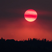 There were major forest fires burning in British Columbia when this sunset photograph was taken in August 2015.  The smoke filled air resulted in the intense red skies.  Sunspots can be seen on the surface of the sun.