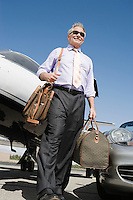 Senior businessman in front of car and airplane, low angle view.