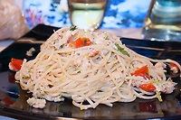 fish sauce spaghetti on black plate side view close-up on blurred background