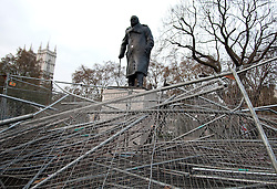 (c) London News Pictures. 10.12.2010. Winston Churchill's Statue stands above damaged railings in Parliament Square. The clean-up operation in Westminster following last night's student demonstration. Picture credit should read: Brian Duckett/London News Pictures