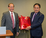 Houston ISD trustee Greg Meyers, left, presents a gift to Director General Louis M. Huang, right, of the Taipei Economic and Cultural Office in Houston, after signing a partnership agreement during a ceremony, December 17, 2015.