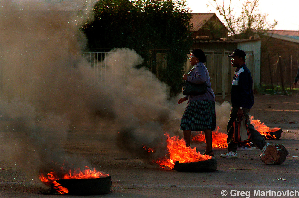 POLITICS TOKOZA SOUTH AFRICA 1991: Residents of Tokoza township go to work past burning tyre barricades erected by African National Congress allied residents and fighters from a Self Defence Unit in Tokoza, South Africa, 1991. Part of The Dead Zone series. (Photo by Greg Marinovich / Getty Images)