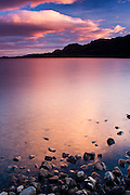 A peaceful lake Kleifarvatn witnesses the light show of sunset as huge clouds drift by and are lit from below
