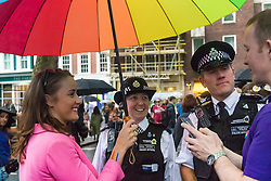 Portland Place, London, June 25th 2016. Thousands of LGBT people and their supporters gather for Pride in London, a colourful celebration of the hard-won rights of lesbian, gay, bisexual and transgender  people. PICTURED: Members of the public and police officers share the cover of an umbrella as the rain falls in Soho Square.