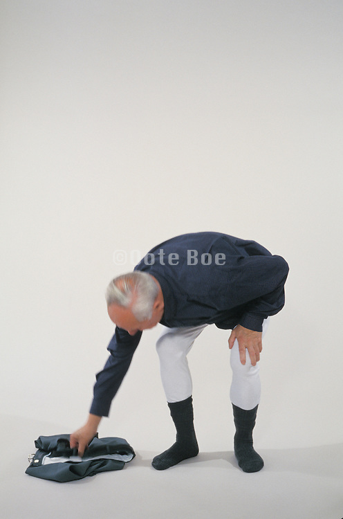 older man dressing himself against a white background
