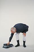 older man dressing himself against a white background