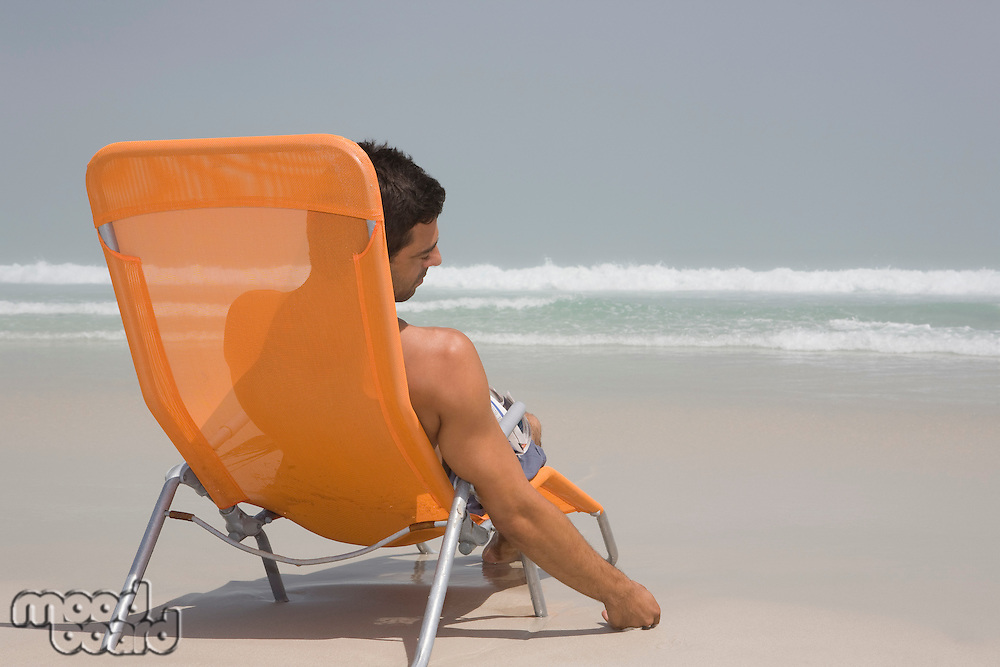 Man sitting on deckchair at beach contemplating
