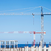 Two cranes at the construction site of a multi-unit building near the sea.<br />