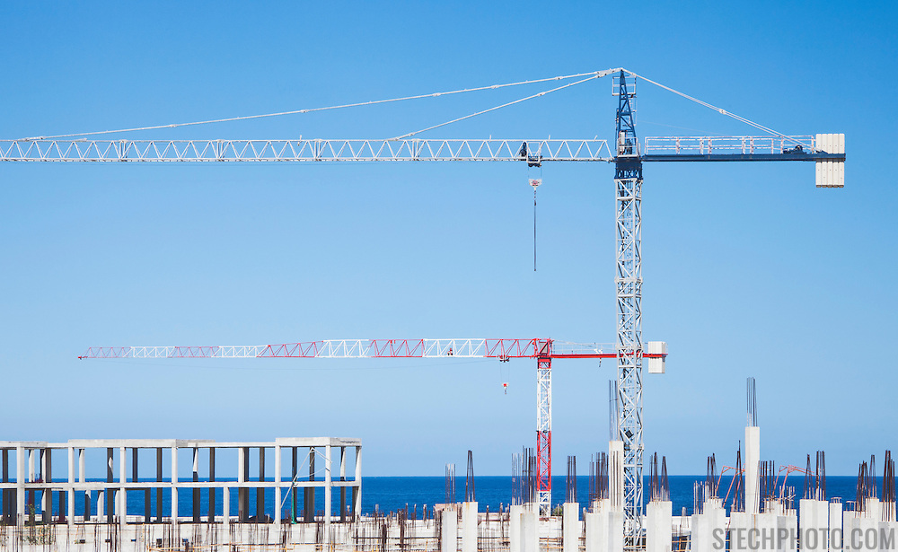 Two cranes at the construction site of a multi-unit building near the sea.<br /> <br /> LICENSING: This image can only be licensed through SpacesImages. Click on the link below:<br /> <br /> http://tinyurl.com/ck8n7bx