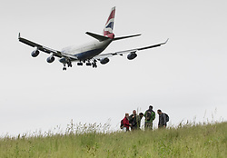 © Licensed to London News Pictures. 05/06/2018. London, UK. A passenger jet comes into land at Heathrow airport as people walk in a field. The government has announced a third runway will go ahead at Heathrow. Photo credit: Peter Macdiarmid/LNP