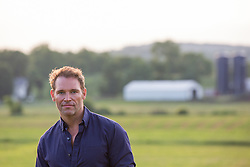 portrait of a handsome man outdoors by a farm