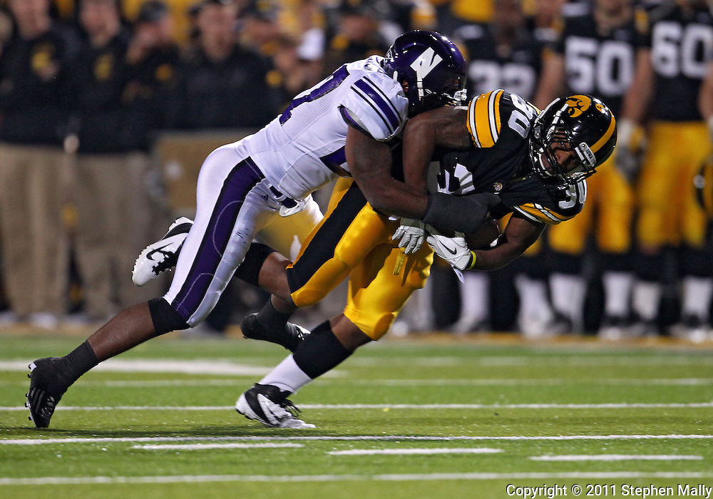 October 15, 2011: Iowa Hawkeyes running back De'Andre Johnson (30) is hit by Northwestern Wildcats safety Jared Carpenter (27) during the second half of the NCAA football game between the Northwestern Wildcats and the Iowa Hawkeyes at Kinnick Stadium in Iowa City, Iowa on Saturday, October 15, 2011. Iowa defeated Northwestern 41-31.