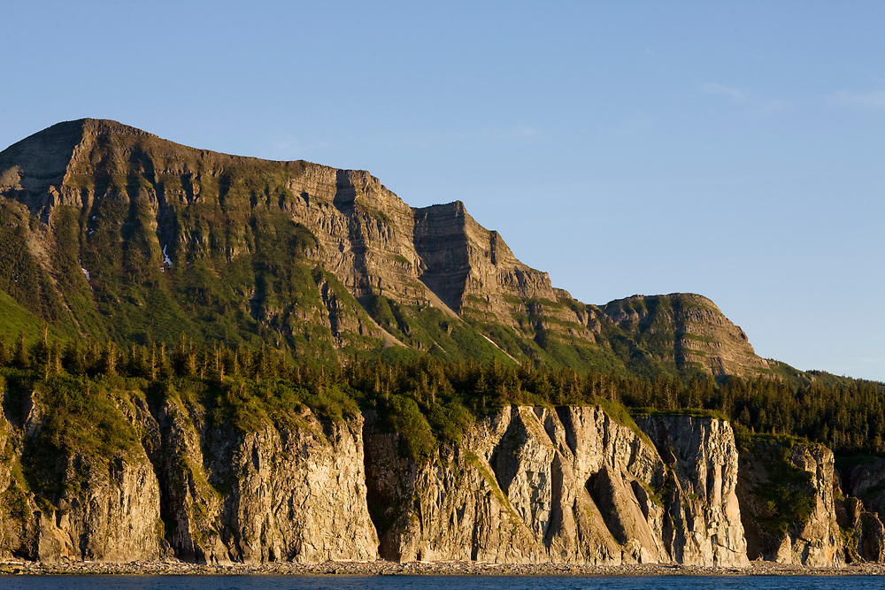 USA, Alaska, Katmai National Park, Setting sun lights cliffs along Cape Nukshak in Hallo Bay on summer evening