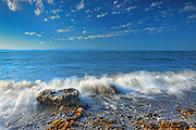 Waves crash against rocky shore of Gulf of St.Lawrence<br /> Iles Aux Coudres<br /> Quebec<br /> Canada