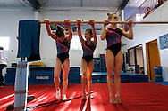 Elite gymnasts Norah Flatley, 16, Victoria Nguyen, 15, and Rachel Gowey, 18, stretch out their toes Friday, May 6, 2016, at the end of practice at Chow's Gymnastics and Dance in West Des Moines. While Gowey is the top prospect for Chow's gym this year, Chow said he sees both Flatley and Nguyen making a run for the Olympics in four years.