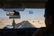 View through a car windscreen of a desert highway road sign for the New Valley, near Luxor, Western Desert, Egypt.