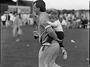 """Guinness Family Day At The Iveagh Gardens. (R83)..1988..02.07.1988..07.02.1988..2nd  July 1988..The family fun day for Guinness employees and their families took place at the Iveagh Gardens today. Top at the bill at the event were """"The Dubliners"""" who treated the crowd to a performance of all their hits. Ireland's penalty hero from Euro 88, Packie Bonner, was on hand to sign autographs for the fans...Image shows this boy hanging on for dear life as dad strolls across the playing field at Iveagh Gardens."""