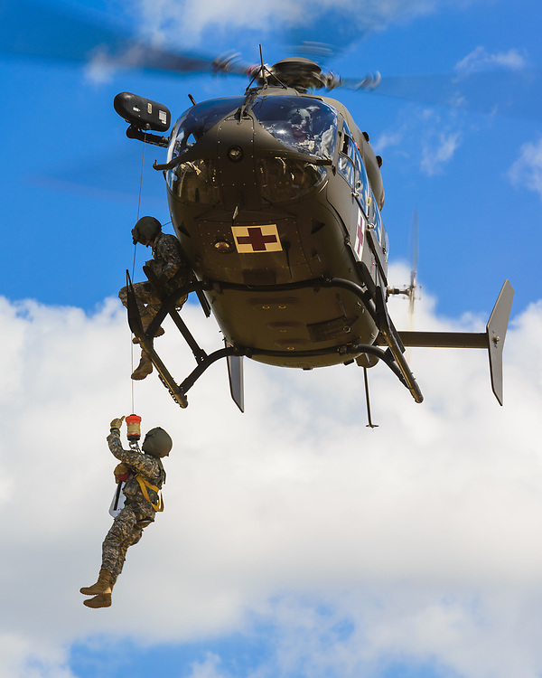 During rescue hoist operations, a flight medic signals to the firefighter on board a UH-72 Lakota MEDEVAC aircraft.