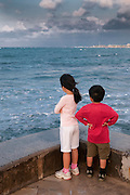 A brother and sister on the pier in Waikiki looking for the sun.
