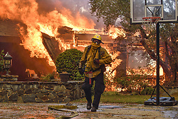 October 9, 2017 - Anaheim, California, U.S. - Fire fighters work to extinguish a fire on Via El Estribo during the Canyon Two Fire. A fast-moving brush fire has burned at least 2,000 acres, prompting evacuations of about 1,000 homes, damaging at least six of them, and sending large plumes of smoke over the city. The nearby eastbound 91 freeway is closed at Imperial Highway. (Credit Image: © Jeff Gritchen/The Orange County Register via ZUMA Wire)