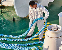 Crew member working with heavy blue rope on the forward deck of the MV World Odyssey. Image taken with a Nikon 1 V3 camera and 70-300 mm VR lens (ISO 320, 96 mm, f/4.8, 1000 sec).