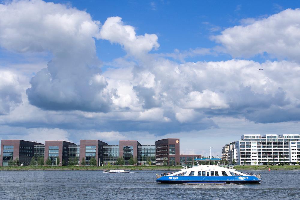 Boten varen over het IJ in Amsterdam voor het hoofdkantoor van de Shell.<br /> <br /> Boats are sailing at the IJ in Amsterdam in front of the Shell head quarters.