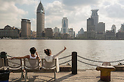 A young couple takes a selfie along the Pudong waterfront with the skyline of old Shanghai, China