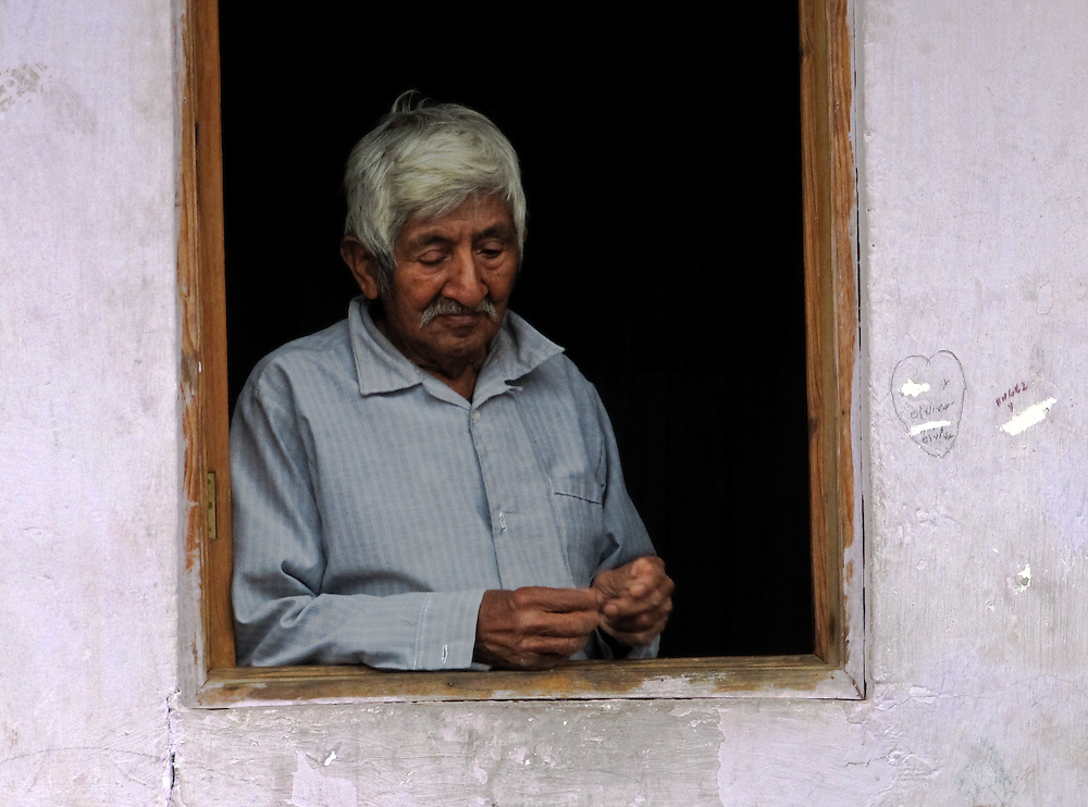 man in window in Xico, state of Veracruz, Mexico