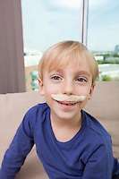 Little boy with artificial mustache smiling