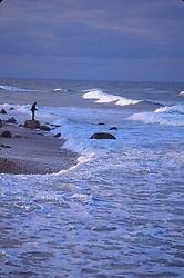 A fisherman casts his line on the surf line on an incoming tide
