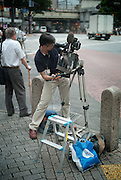 Shibuya, Tokyo, Japan - 22nd of July 2009 - A cameraman filming partial solar eclipse (75%).