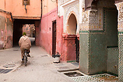 MARRAKESH, MOROCCO - 19TH APRIL 2016 - A local to Marrakesh cycles past the Zaouia / zawiya burial tomb shrine site of Sidi Ben Slimane - Shaykh Muhammad ibn Sulayman al-Jazuli, Marrakesh, Morocco. <br />
