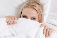 Close-up portrait of young woman covering face with bed sheet