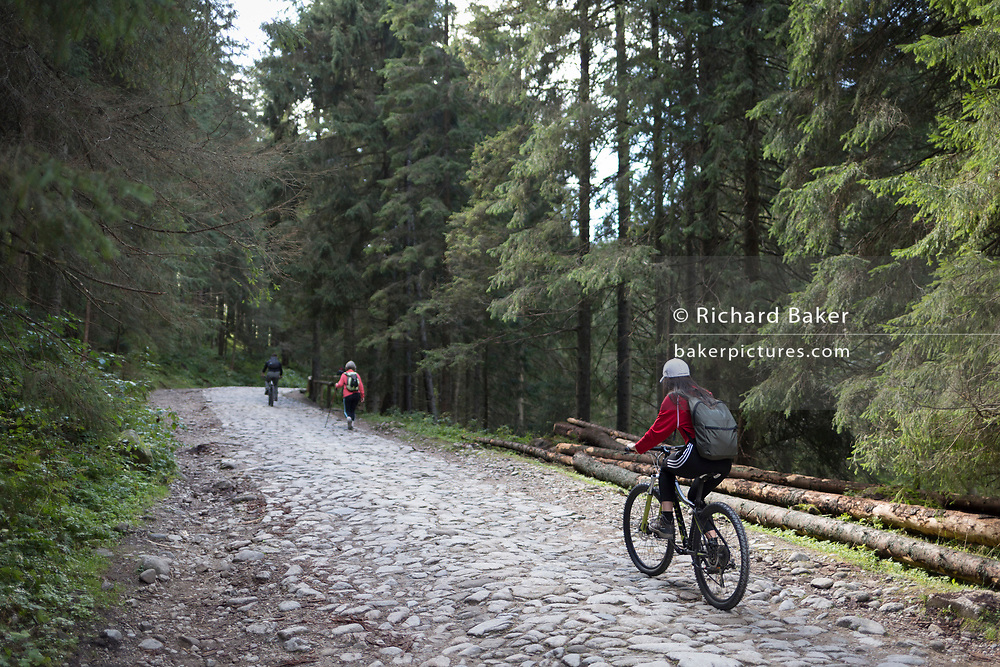 Cyclists climb along a cobbled road in Dolina Chocholowska, a hiking route in the Polish Tatra mountains, on 17th September 2019, near Zakopane, Malopolska, Poland.