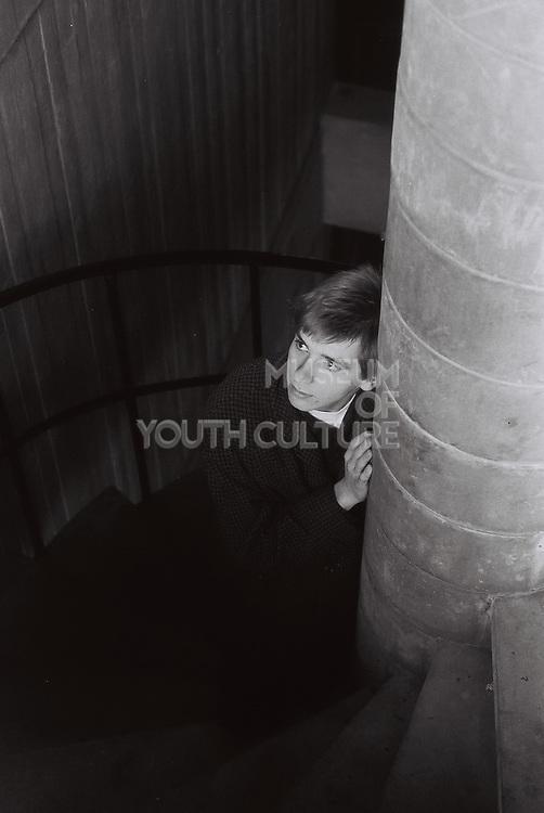 Teenager standing on spiral stairwell, Essex, UK, 1983