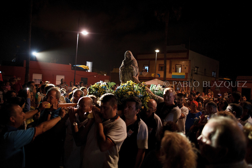 15/08/2016. Fishermen carry the image of the Virgin of Palm back to the sea at El Rinconcillo beach during the yearly Virgin of Palm maritime pilgrimage on August 15, 2016 in Algeciras, Spain. The Our Lady of Palm maritime pilgrimage in Algeciras dates back to 1975 and takes place annually when fishermen rescue the submerged virgin from the deep sea. Worshippers amid thousands of visitors await its arrival at the Rinconcillo beach. The devotion for the Virgin of Palm comes from the seventeenth century when a ship coming from Italy docked at Algeciras port to wait out bad weather. According to legend, once the crew of the ship removed a box with an image of the Virgin from its cargo the weather turned and the sea's tides were calmed. (© Pablo Blazquez)