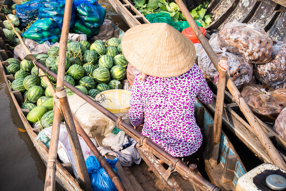 A woman selling watermelons from her boat at Phong Dien Floating Market on the Can Tho River in the Mekong Delta region of Vietnam