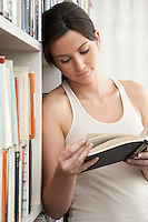 Young woman reading book leaning against bookshelf