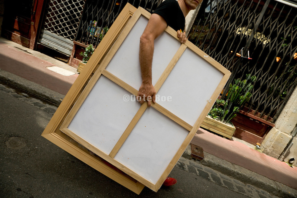 artist walking with painting under his arms through the street