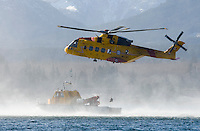 A Cormorant search and rescue helicopter hovers over a rescue boat during a training exercise near CFB Comox.  Courtenay, Comox Valley, Vancouver Island, British Columbia, Canada.