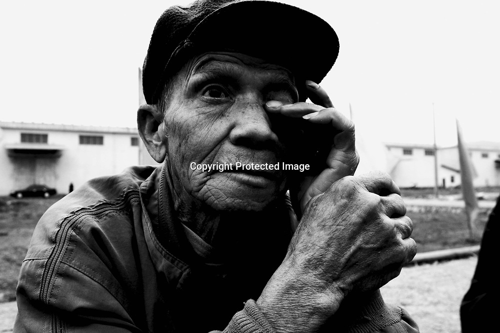 """CHONGZUO-APRIL 10: an elderly farmer waits outside the   """"Lifetime Express"""" train, a movable hospital for eye-catarct surgeries, April 10, 2004 in Chongzhou, Guangxi province, China. Guangxi is one of the poorest places in China with an annual income of USD 120-250 per year for peasants. Without Lifetime Express, a Hong Kong based Non Governmental Organization (NGO) that performs cataract surgeries for free, many people in rural areas would remain partly blind as the official fee for such surgeries in China about USD 600 is out of reach for all of them."""
