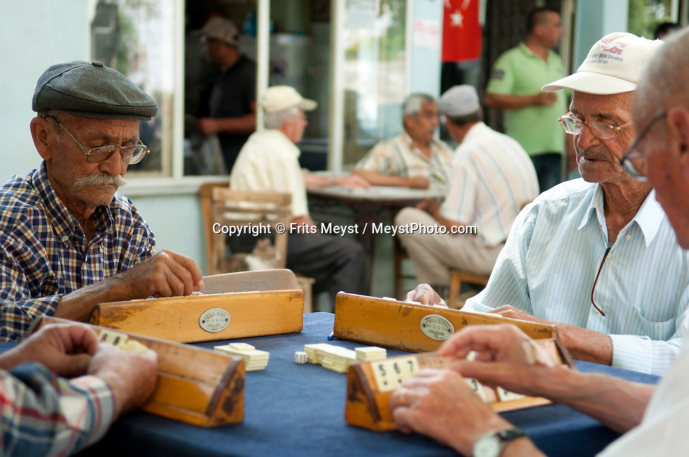 Ba?yüzü village, Kozak, Ayvalik, Western Turkey, July 2011. Old men play a game of Okey in the Tea House of the village. the Kozak region between Bergama and Yavalik is locally known for it's pinenut harvest. Turkey among the top 3 of Pinenut export in Europe.  The Turkish Aegean coastline is littered with historical sites dating back to the Greek classical era. Photo by Frits Meyst/Adventure4ever.com.
