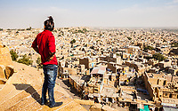 A man standing atop the walls of Jaisalmer Fort looks out over the city of jaisalmer, Rajasthan, India.