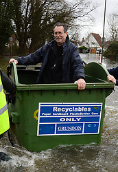 A local resident is rescued in a recycle bin as floods hit Egham, United Kingdom, Wednesday, 12th February 2014. Picture by Andrew Parsons / i-Images