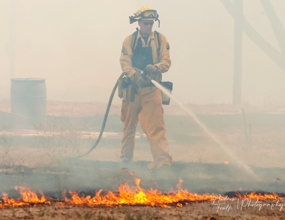 /Andrew Foulk/ For The Californian/ .A firefighter puts out a hot spot near lindenberger road in Menifee during a brush fire that consumed over 25 acres and threatened structure. ...